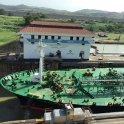 Ship passing through Panama's Miraflores Lock with Visitor Center in the background